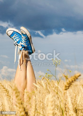 Sexy summer field legs sticking out of the wheat over dramatic blue sky
