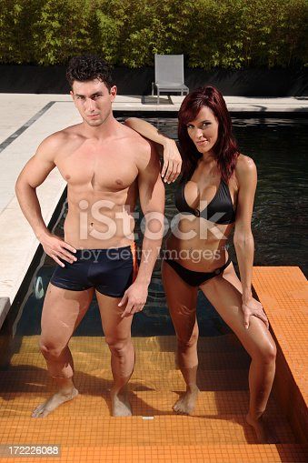 A sexy couple in swimmwear stand on the steps of a swimming pool.
