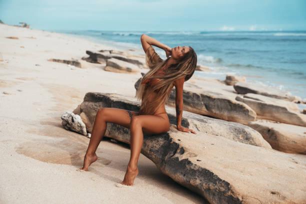 sexy tätowierte mädchen im roten badeanzug am strand posieren. schöne blonde frau mit langen haaren entspannung am meer. konzept der sportliche modell bademode - haare ohne lockenstab wellen stock-fotos und bilder