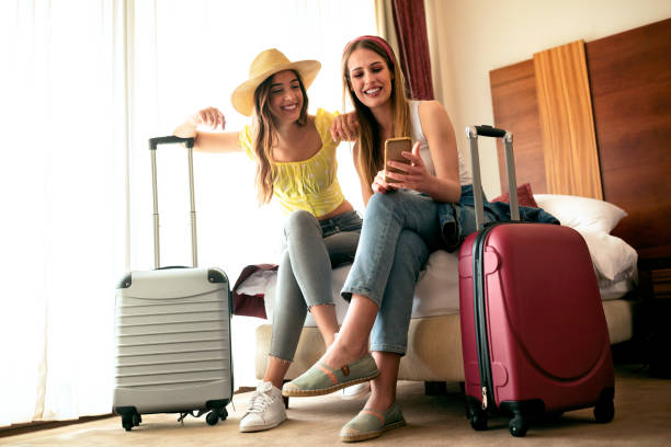 Sexy traveling girls and their luggage stock photo
