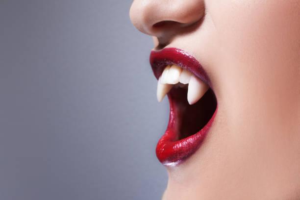 sexy vampir. frauen lippen mit rotem lippenstift. schreienden mund mit vampirzähne - vampir schminken frau stock-fotos und bilder