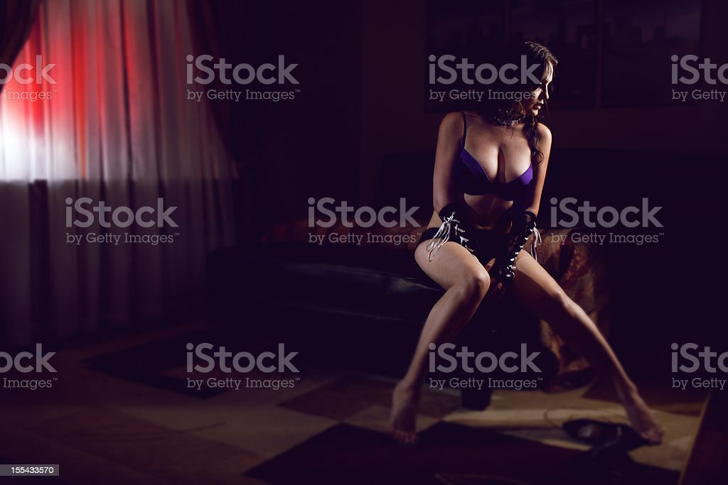 Sexy voluptuous woman sitting in bedroom wearing lingerie stock photo