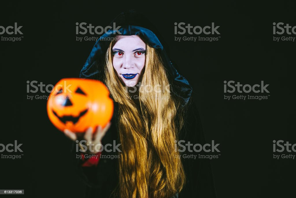 Sexy Witch Giving Plastic Pumpkin stock photo