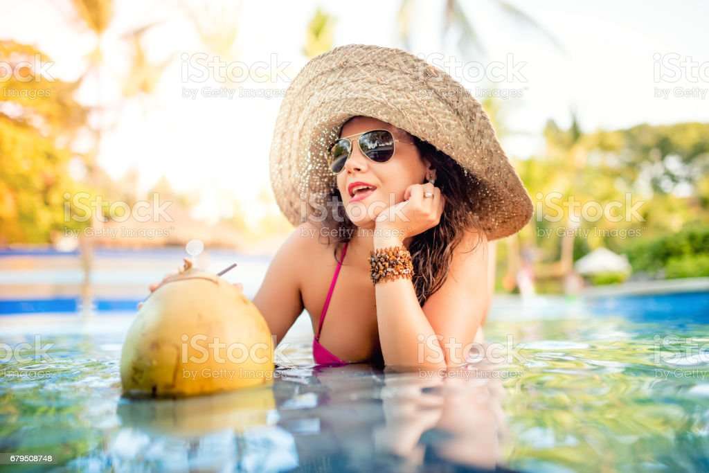 Sexy woman enjoying a coconut cocktail at pool bar while having a good time in water royalty-free stock photo