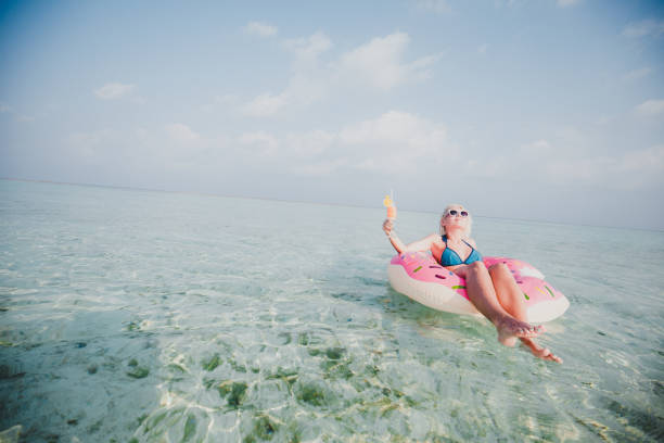 Sexy woman floating on water and have cocktail time in ocean, Maldives stock photo