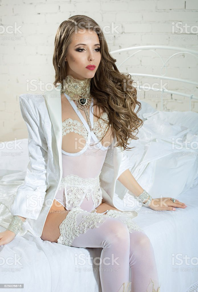 Sexy woman in beautiful white lingerie on white bed stock photo