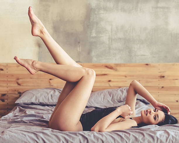 sexy woman in bedroom - human leg stock photos and pictures