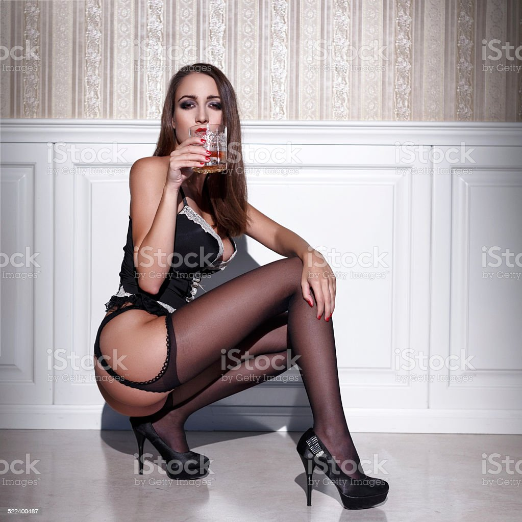 sexy woman in corset and stockings squat with whiskey stock photo