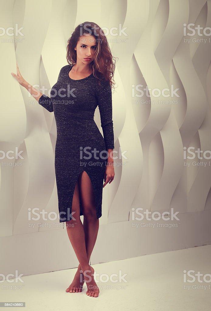 Sexy woman in fashion grey dress posing near paper wall stock photo
