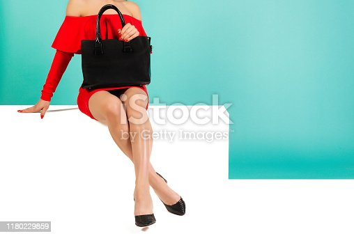 539468216 istock photo Sexy woman in high heels with black handbag on a blue background. 1180229859