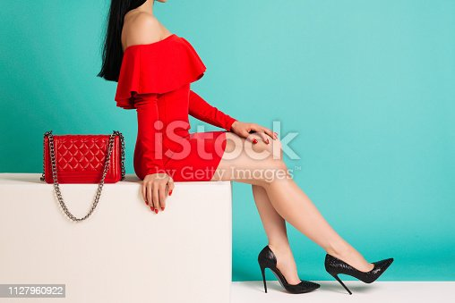 539468216 istock photo Sexy woman in high heels with red bag on a blue background. 1127960922