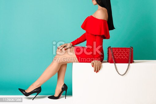 istock Sexy woman in high heels with red bag on a blue background. 1129067386