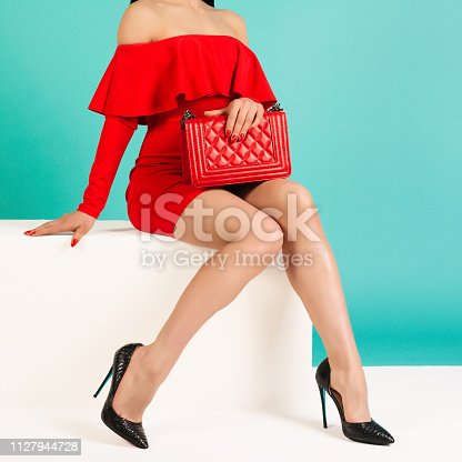 539468216 istock photo Sexy woman in high heels with red handbag on a blue background. 1127944728