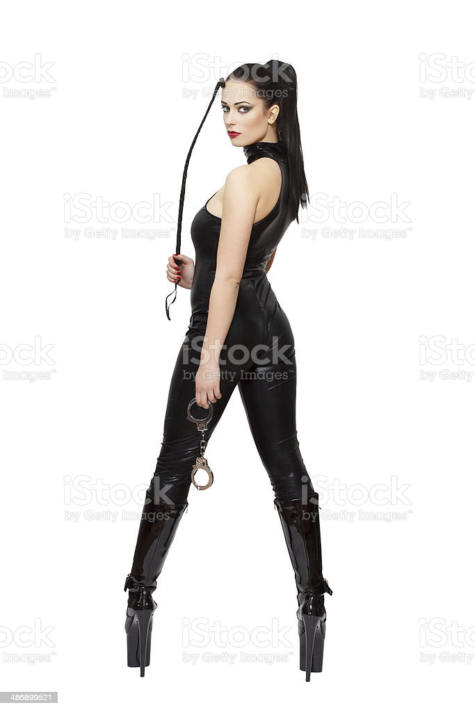 Sexy woman in latex catsuit and boots holding whip stock photo