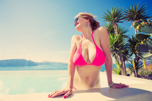 Sexy woman in pink bikini by the pool. Vintage style filter. stock photo