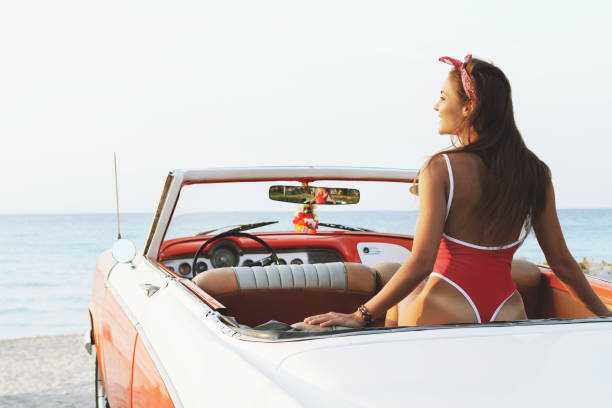 sexy woman in red swimsuit and retro cabriolet car - aura stock photos and pictures