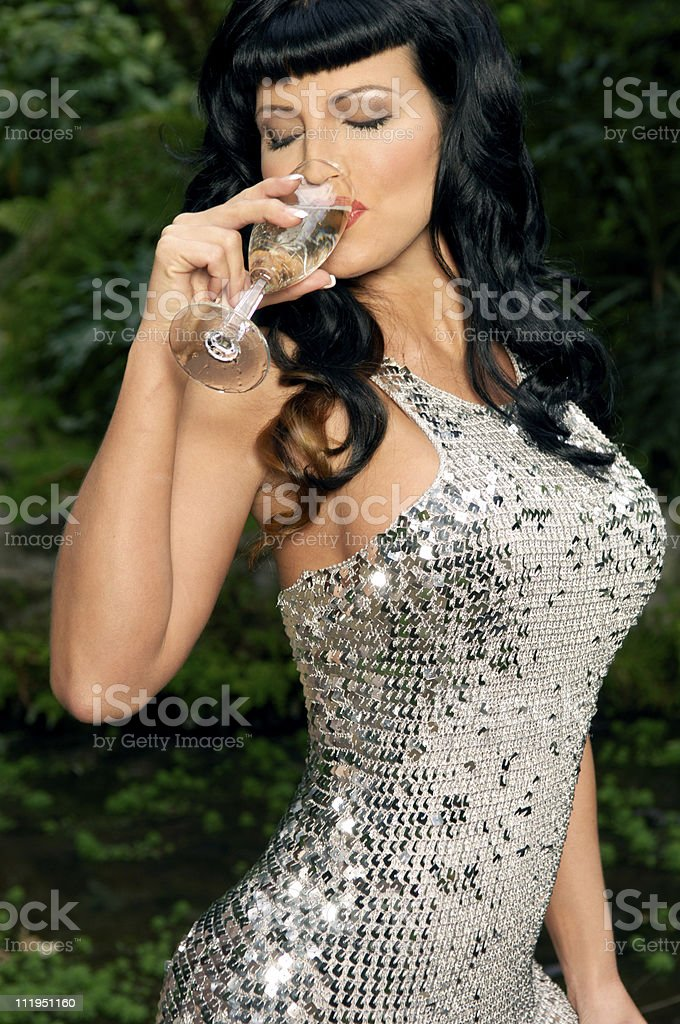 Sexy Woman in Sequined Dress Sips Champagne stock photo