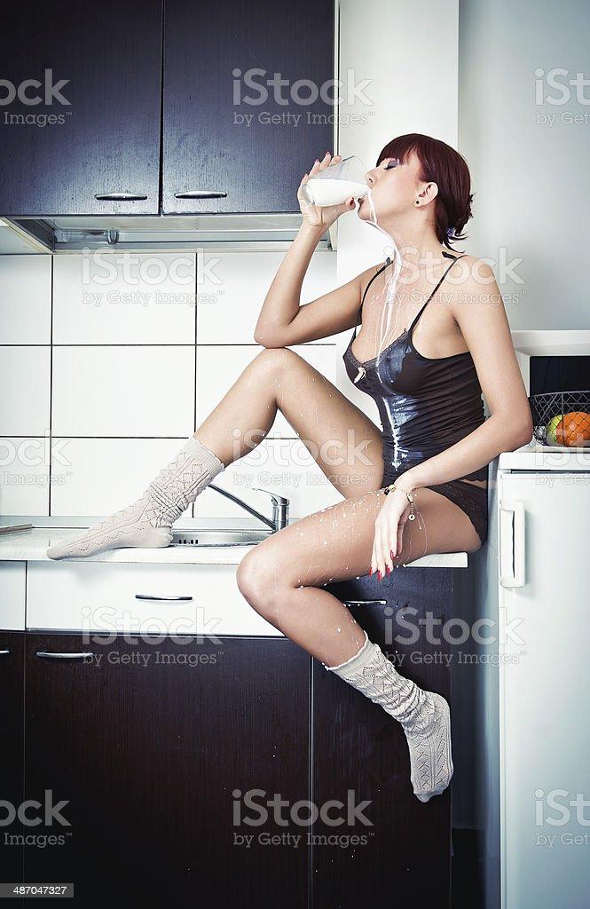 Sexy Frau in T-shirt und Socken trinkt Milch in der Küche – Foto
