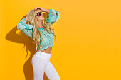 Beautiful blond woman in sunglasses, turquoise lace blouse and white leggings is posing in sunlight with arms raised. Three quarter length studio shot on yellow background.