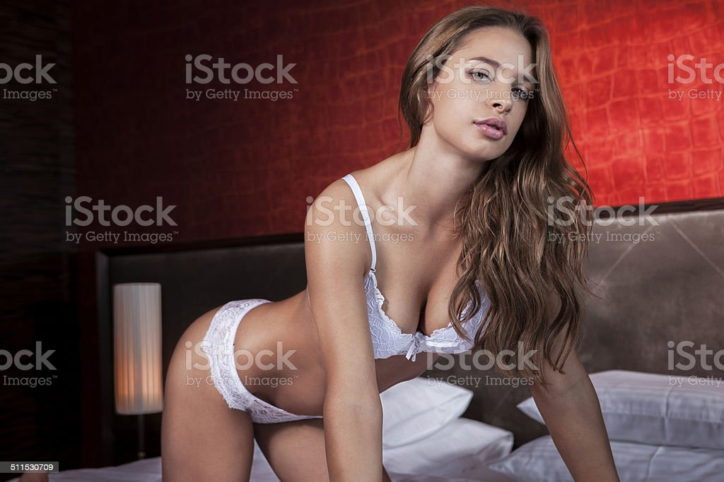 Sexy woman in white lingerie posing on bed stock photo