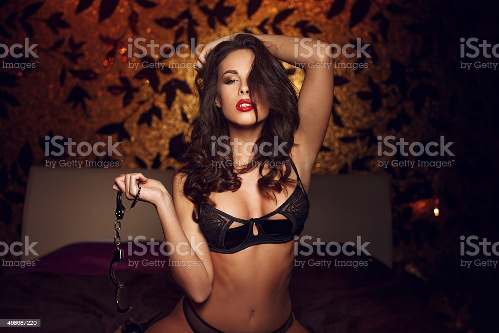 Sexy woman kneeling and holding handcuffs on bed stock photo