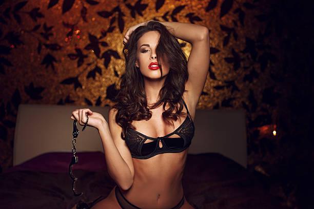arrodillarse y sexy mujer sosteniendo un pie atado al suelo sobre la cama - esposa fotografías e imágenes de stock