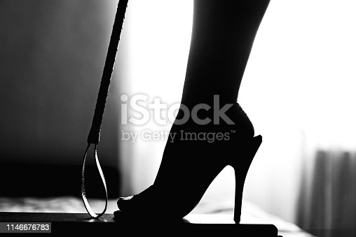 sexy woman legs in high heels and riding crop. bdsm spanking fetish concept