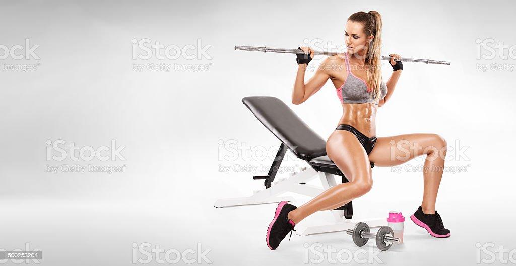 sexy femme assise sur un banc de musculation et d'entraînement avec haltères - Photo