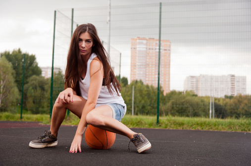 Sexy Woman Sitting On Basketball Stock Photo - Download Image Now
