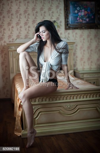 istock sexy woman sitting on bed talking by phone 520562193