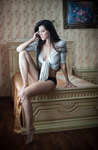 sexy Frau sitzen auf Bett am Telefon reden – Foto