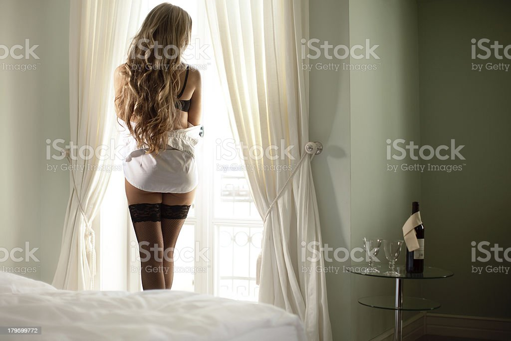 Sexy woman standing in bedroom looking out window stock photo