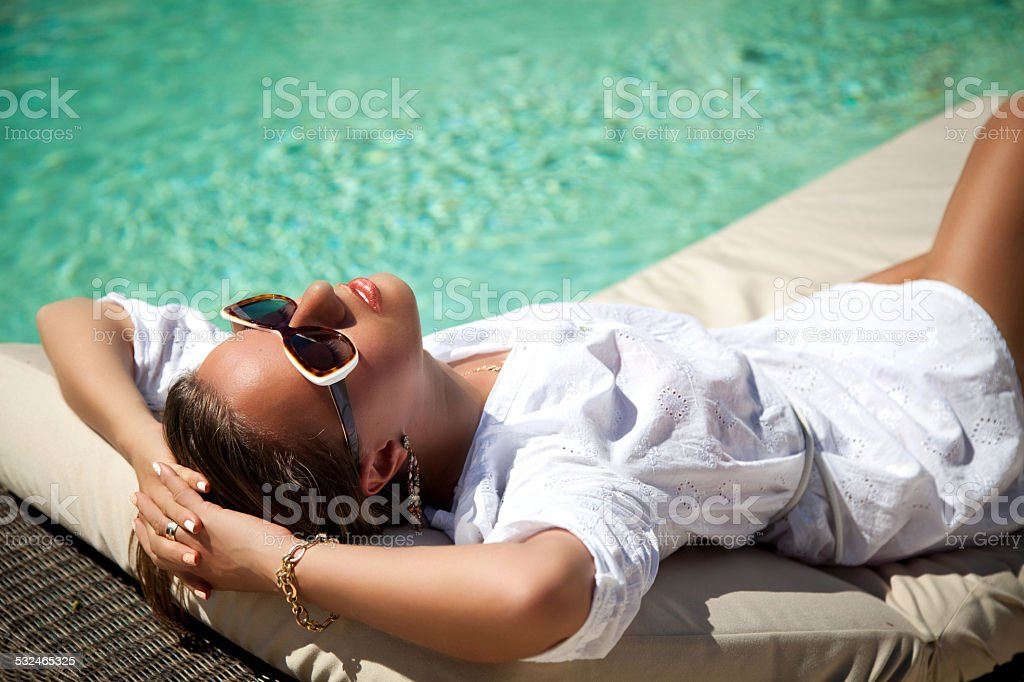 Sexy woman sunbathing at pool resort stock photo