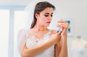 Young woman picking her wedding dress, soon to be married, love and relationship, marriage, beautiful young woman wearing designer wedding dress in beautiful wedding salon or bridal shop, taking photos with her smart phone