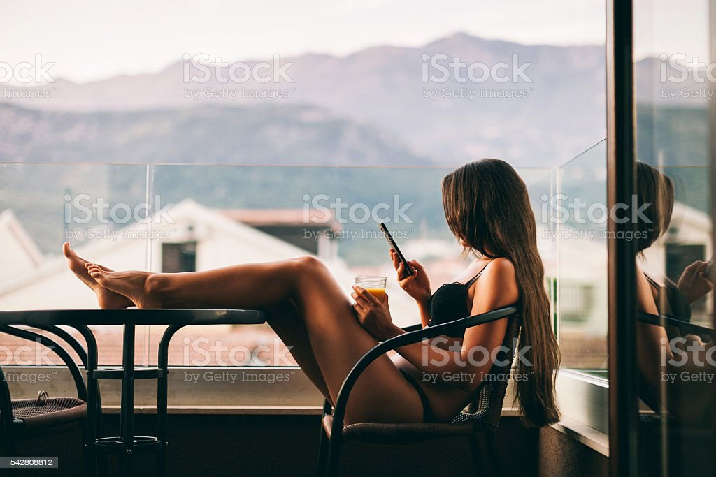 sexy Woman using smartphone at home stock photo