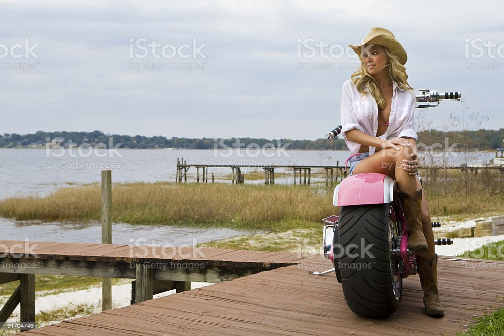 Sexy Woman Wearing A Cowboy Hat Sitting on Chopper Motorbike stock photo