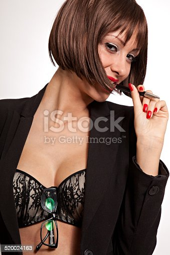 istock Sexy woman with black suit and bra sucking pen 520024163