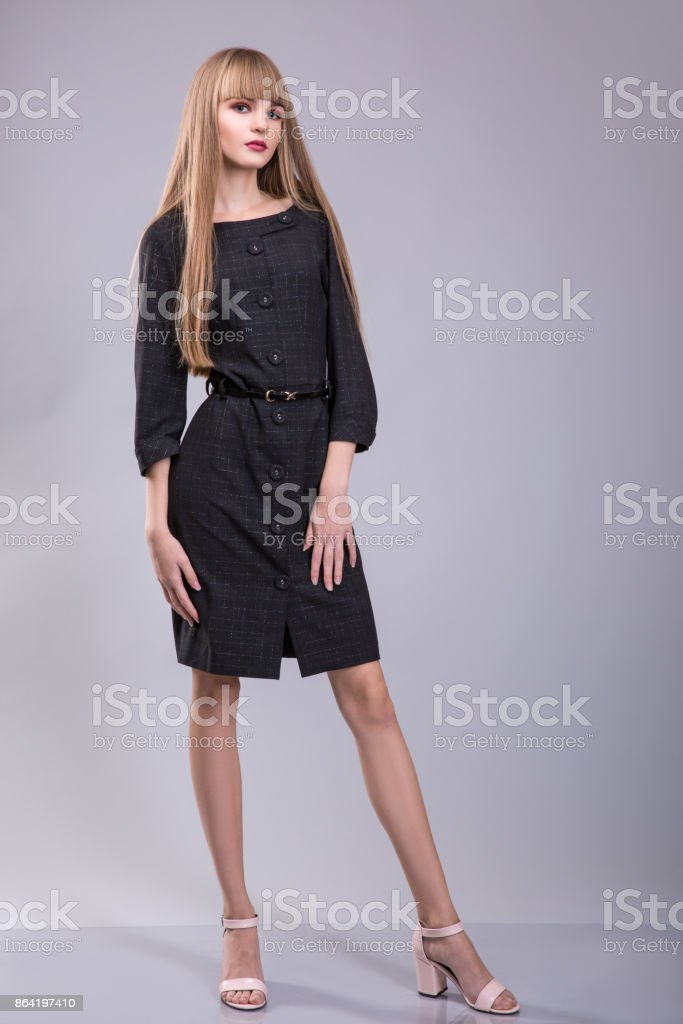 sexy woman with blond hair wear in black dress over grey background royalty-free stock photo