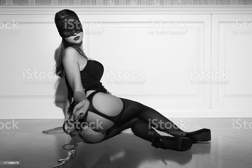 Sexy woman with handcuffs sit on floor black and white stock photo
