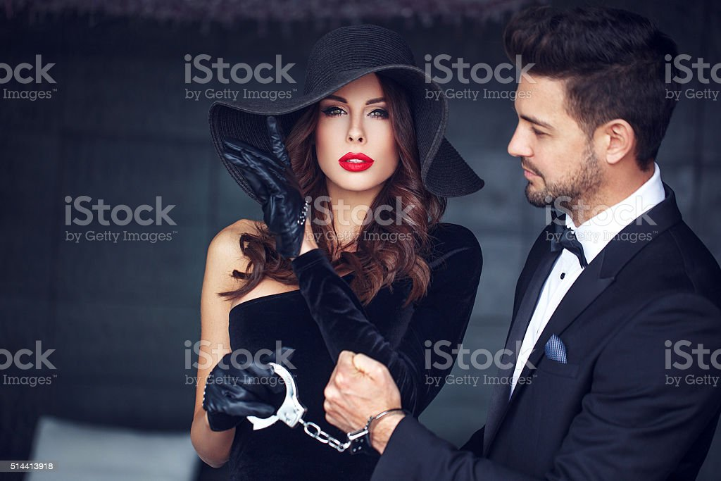Sexy woman with hat and handcuffs holding man stock photo