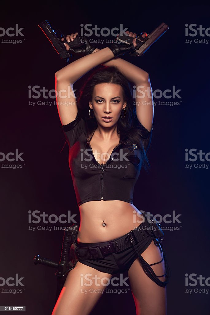 Sexy woman with police uniform in studio Sexy woman with police uniform in studio on dark red and blue background Adult Stock Photo