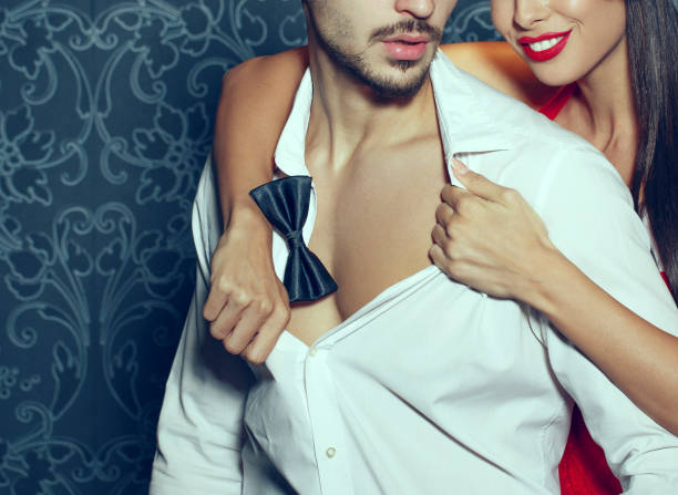 Sexy woman with red lips undressing trendy macho man indoor stock photo