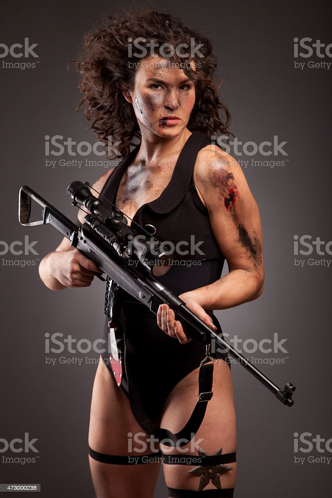 Sexy woman with weapon on dark background. Riot girl. stock photo