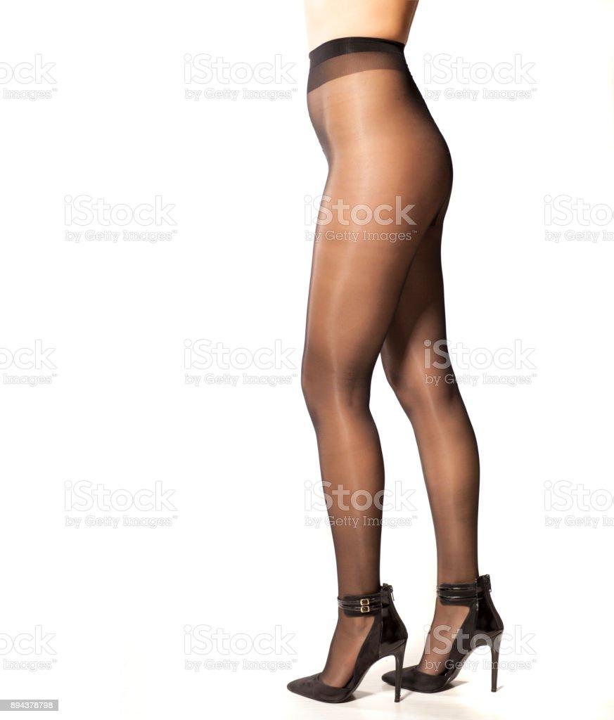 f0c1eb0d71 Piernas de mujer sexy en medias de nylon y tacones altos sobre fondo blanco  foto de