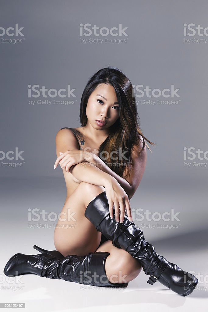 Sexy Young Asian Woman in Black Leather Boots - Stock image .