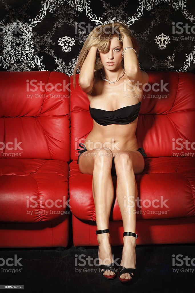 Sexy young blonde lady in black lingerie on red sofa royalty-free stock photo