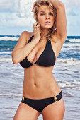 """Photo of a sexy young blonde woman wearing a black bikini, posing on a remote Hawaiian beach."""
