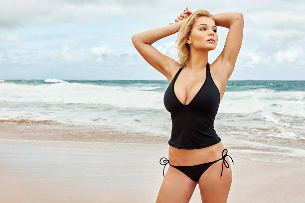 sexy young blonde woman in black tankini posing on beach - busty women in bikinis stock pictures, royalty-free photos & images