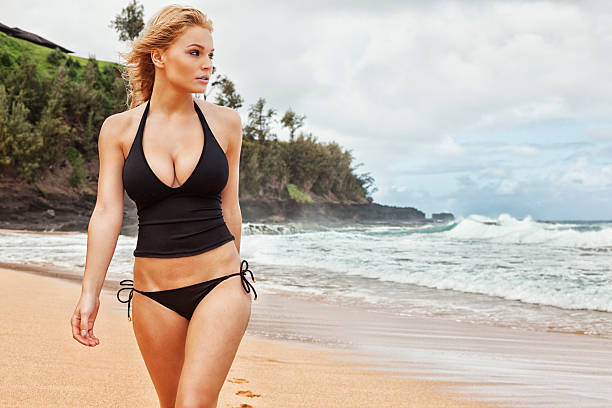 sexy young blonde woman in black tankini walking on beach - busty women in bikinis stock pictures, royalty-free photos & images