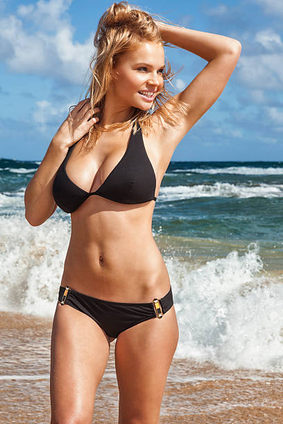 sexy young blonde woman on beach in black bikini - curvy voluptuous women stock photos and pictures